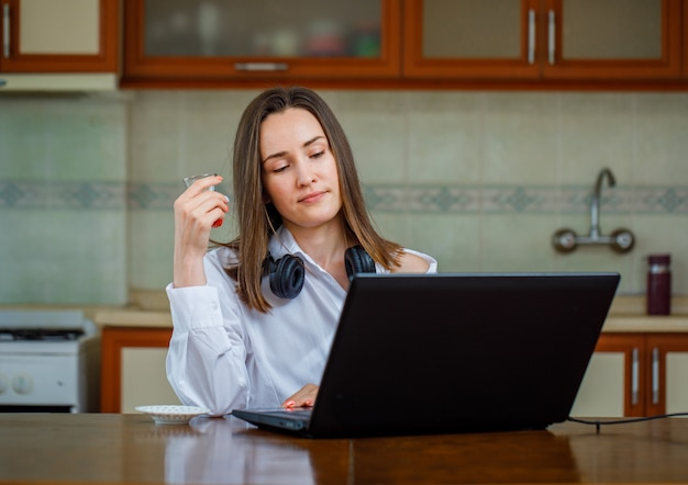 Donna splendida in camicia bianca che guarda qualcosa mentre tenendo un bicchiere di tè in cucina