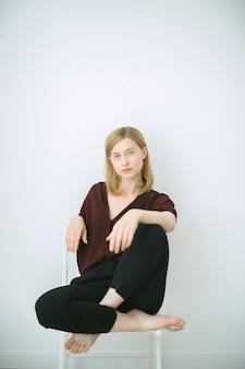 Donna splendida in camicia marrone e pantaloni neri che si siedono su una sedia e che guardano nella sala con il fondo bianco.