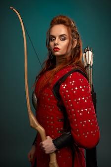 Donna splendida in tunica medievale con arco e frecce.