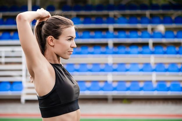 Donna sportiva adatta che fa allenamento di forma fisica e che risolve sullo stadio di mattina