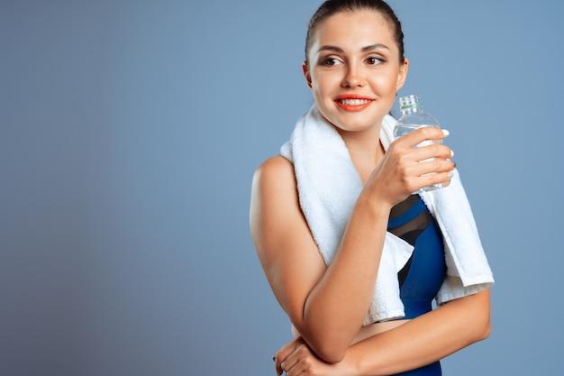 Donna sportiva adatta che tiene la bottiglia di acqua minerale in sua mano