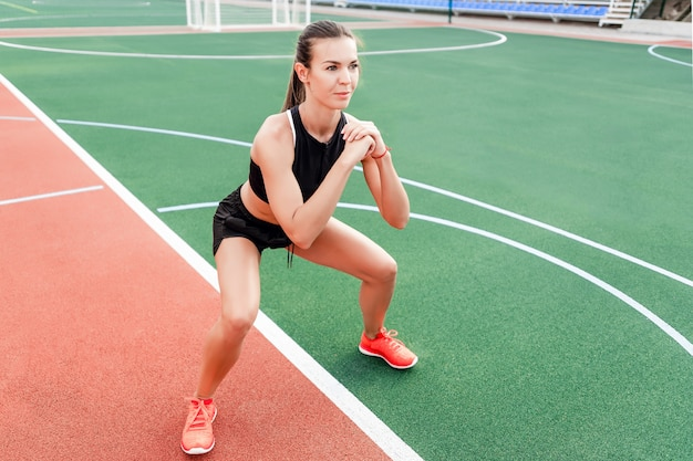 Donna sportiva allenamento e allenamento sullo stadio al mattino
