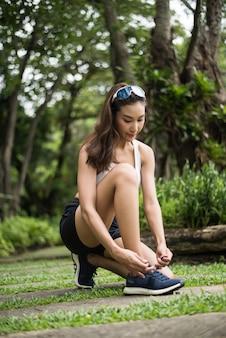 Donna sportiva attraente che lega lacci delle scarpe si prepara per fare jogging. concetto di salute e sport