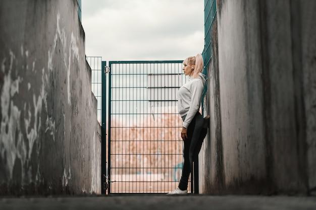 Donna sportiva caucasica che si appoggia sulla parete e che riposa dopo l'esercizio. tempo d'autunno, a figura intera, vista laterale.