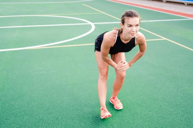 Donna sportiva che allunga fuori sullo stadio prima dell'allenamento di mattina