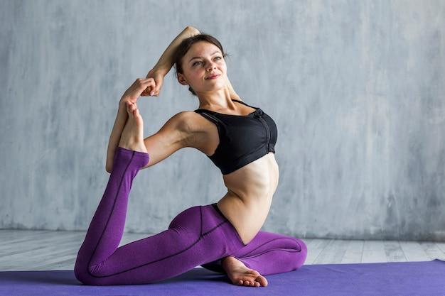 Donna sportiva che allunga la sua gamba dietro