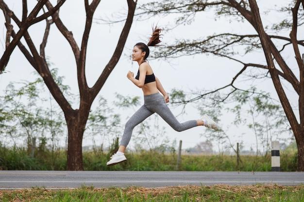 Donna sportiva che corre e che salta nel parco