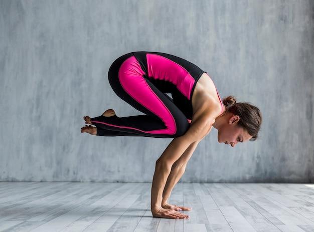 Donna sportiva che esegue una posa di yoga del corvo