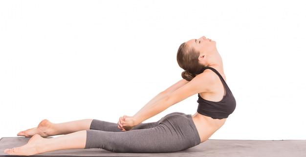 Donna sportiva che fa esercizio di yoga nella posa del gatto.