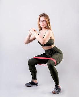 Donna sportiva che fa gli edifici occupati facendo uso dell'elastico di resistenza isolato su fondo grigio