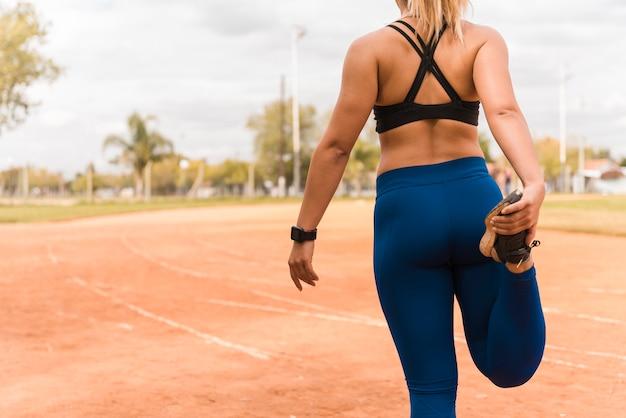 Donna sportiva che si estende sulla pista dello stadio