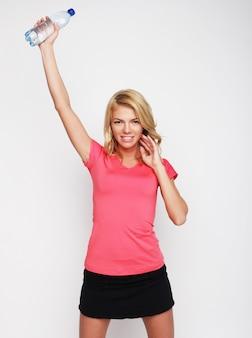 Donna sportiva con bottiglia d'acqua