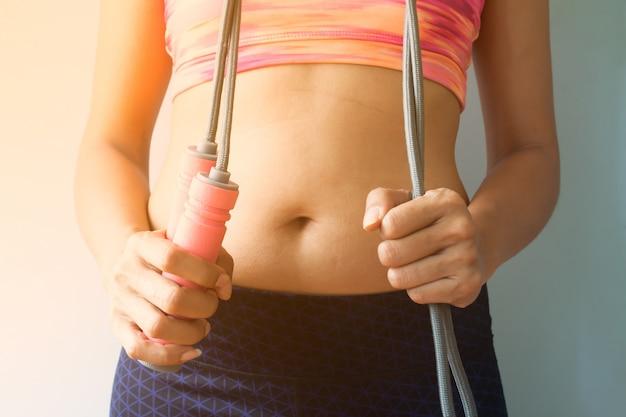 Donna sportiva con la corda di salto, concetto sano e stante a dieta