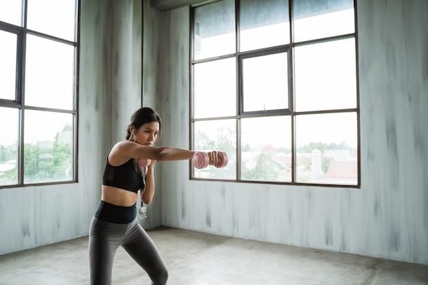 Donna sportiva con la testa di legno che fa esercizio del peso