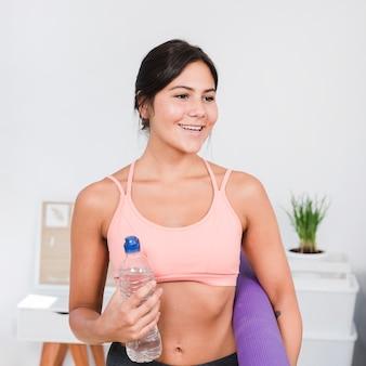 Donna sportiva con tappetino yoga