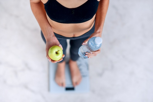 Donna sportiva con un corpo perfetto che misura il peso corporeo su bilance elettroniche e che tiene una bottiglia d'acqua e una mela verde