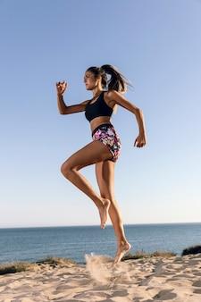 Donna sportiva di angolo basso che salta in spiaggia
