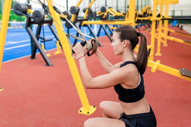 Donna sportiva di forma fisica che fa trx che si prepara all'aperto sullo stadio
