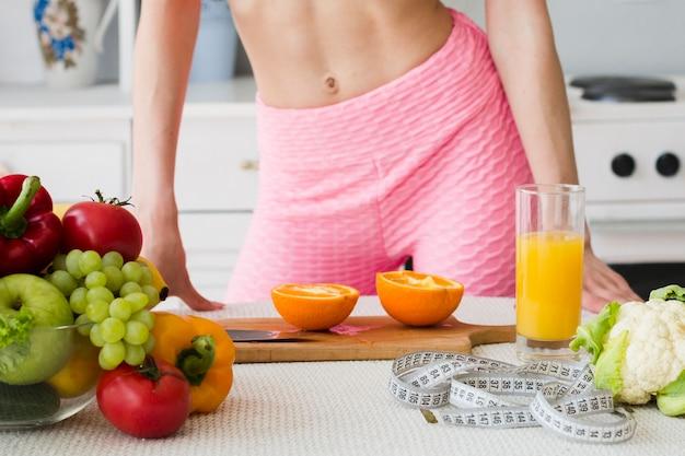 Donna sportiva in cucina con succo sano