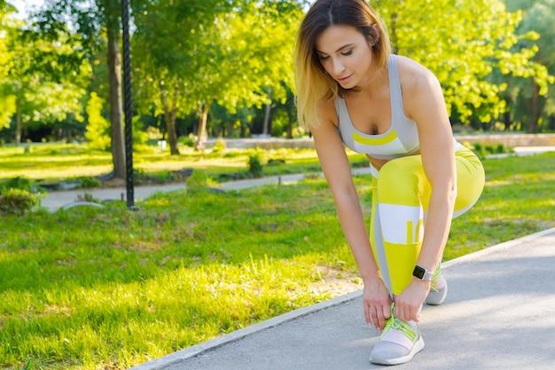 Donna sportiva nella posa di inizio corrente nel parco della città