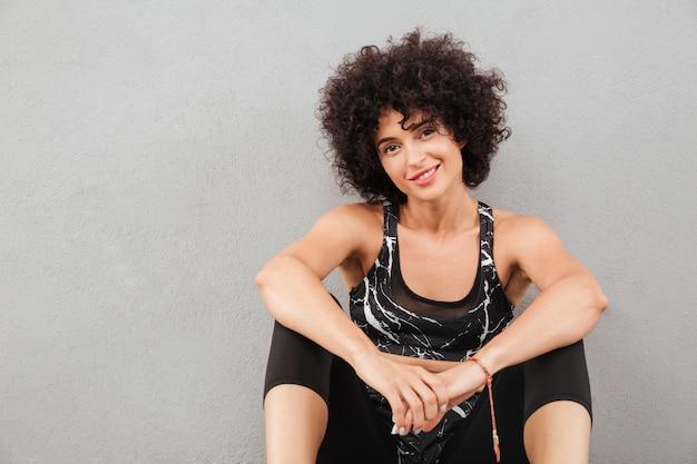 Donna sportiva piacevole che si siede sul pavimento
