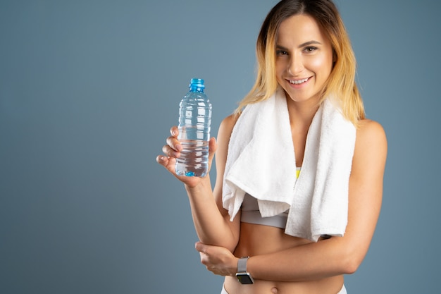 Donna sportiva sopra fondo grigio che tiene una bottiglia di acqua