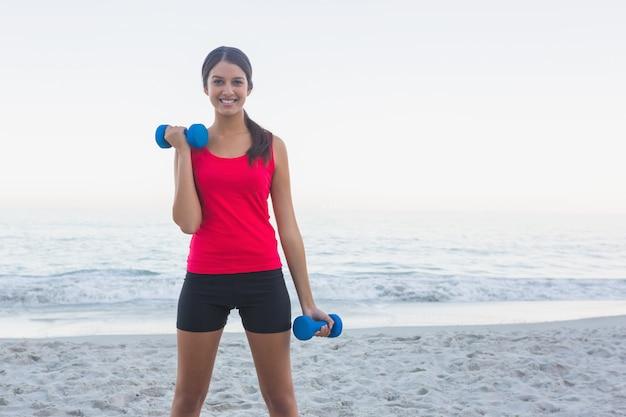 Donna sportiva sorridente che si esercita con i dumbbells
