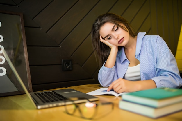 Donna stanca con il computer portatile nella caffetteria alla fine della giornata