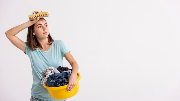Donna stanca del colpo medio con il canestro di lavanderia e della spazzola