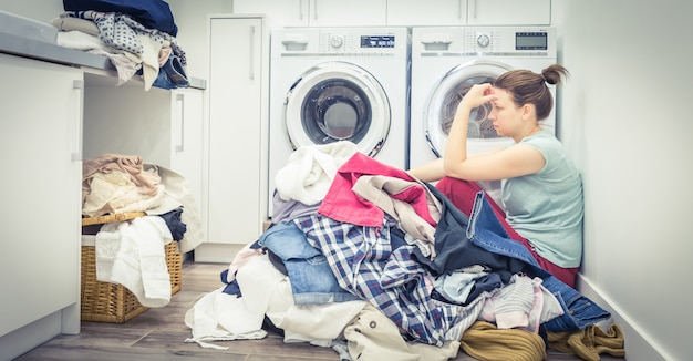 Donna stanca triste nella stanza di lavanderia, tonalità blu
