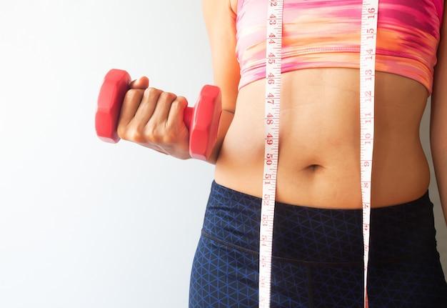 Donna stante che tiene il concetto di manubrio rosso, sano e dieta
