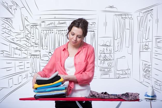Donna stiratura abbigliamento nella sua stanza