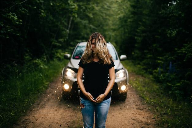 Donna strana, strana, irriconoscibile e sconosciuta con lunghi capelli lussureggianti sul viso in piedi da solo davanti alla grande macchina nella foresta pluviale. concetto di film horror.