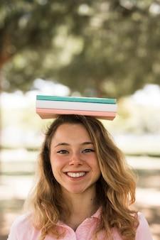 Donna studentessa con libri sulla testa