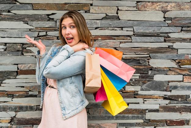 Donna stupita che sta con i sacchetti della spesa variopinti