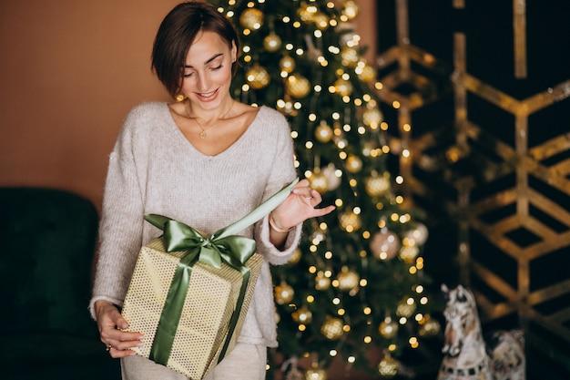 Donna su natale che tiene un regalo di natale dall'albero di natale
