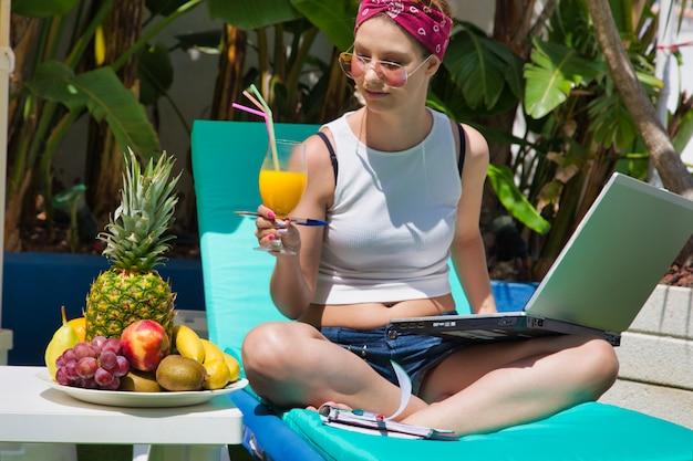 Donna su un lettino con un piatto di frutta e un bicchiere di succo in mano mentre si lavora con un computer portatile