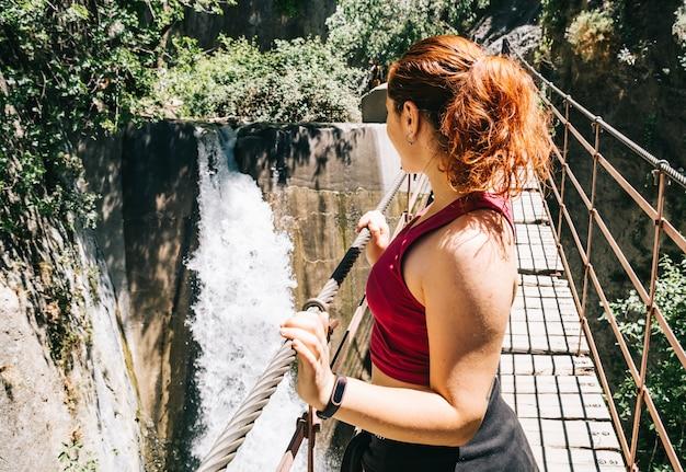 Donna su un ponte che esamina la cascata, los cahorros, granada, spagna