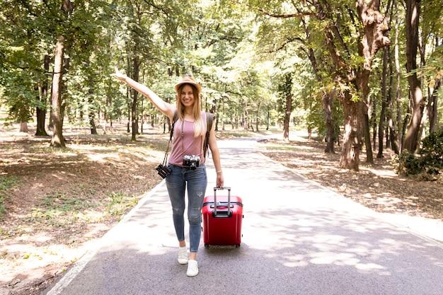 Donna su un sentiero forestale che sorride alla macchina fotografica