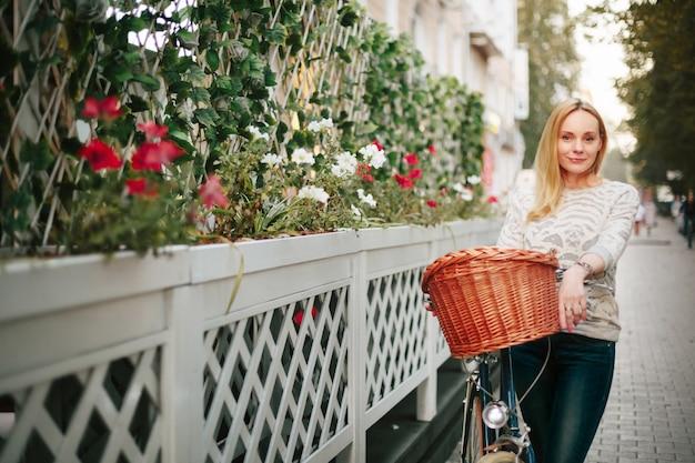 Donna su una bicicletta d'epoca in strada