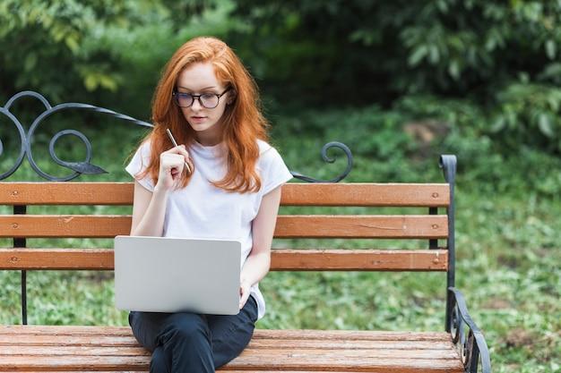 Donna sul banco di legno con laptop e penna