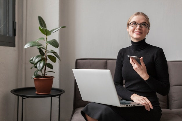 Donna sul divano con cellulare e laptop