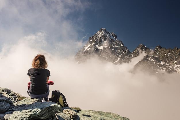 Donna sulla cima dell'alta montagna, picco di montagna maestoso del paesaggio drammatico sopra le nuvole, chiaro cielo blu