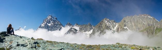 Donna sulla cima di alta montagna, drammatico paesaggio maestoso picco di montagna sopra le nuvole