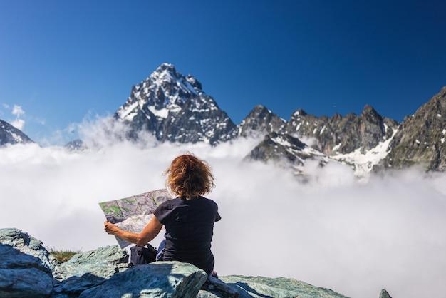 Donna sulla cima di alta montagna, guardando la mappa, maestoso picco di montagna sopra le nuvole