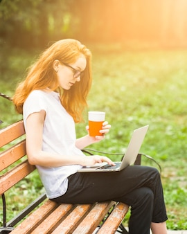 Donna sulla panchina con computer portatile e bevande
