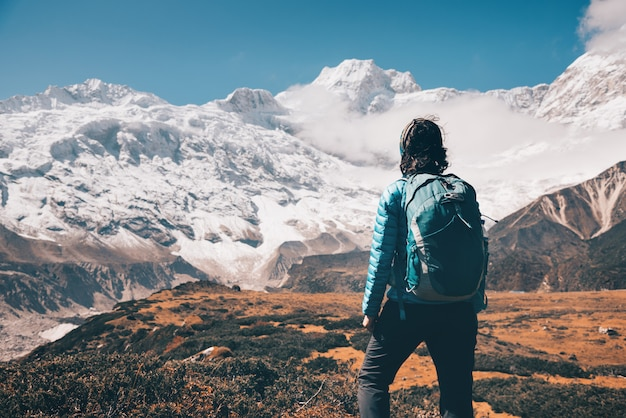 Donna sulla pietra e la valle di montagna