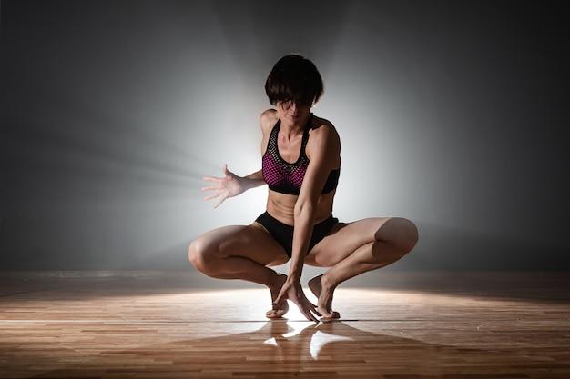 Donna sulla pista da ballo. ballerino femminile del palo che balla su un fondo nero