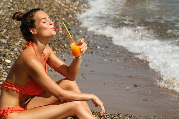 Donna sulla spiaggia con un bicchiere di cocktail