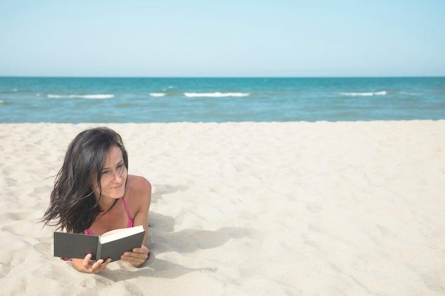 Donna sulla spiaggia leggendo un libro